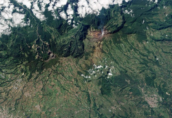 """Turrialba Volcano, located in central Costa Rica, emits a translucent plume of volcanic gases in this natural-color satellite image from January 21, 2010. According to the RED Sismológica Nacional (Costa Rican National Seismological Network), activity at the volcano increased markedly on January 4, 2010. Strong, long-lasting volcanic tremors were accompanied by gas plumes over the volcano, and emissions of ash began on January 5th. The """"jet-type noise"""" of gas and ash rushing out of fumaroles was heard several kilometers away. On January 21, Nacion.com reported that potato and carrot farmers were asked to leave fields near the volcano's summit due to further increases in gas emissions. The barren summit region of the 3,340-meter- (10,960-foot-) high Turrialba appears gray and brown, while the volcanic plume is a hazy blue. Fields and pastures are light green, in contrast to dark green forest that covers the high-elevation ridges. Since 2007, frequent acid rain showers caused by activity at the volcano killed or damaged much of the vegetation to the southwest of the summit, leaving the area brown and orange. This image was acquired by the Advanced Land Imager (ALI) aboard NASA's Earth Observing-1 (EO-1) satellite."""