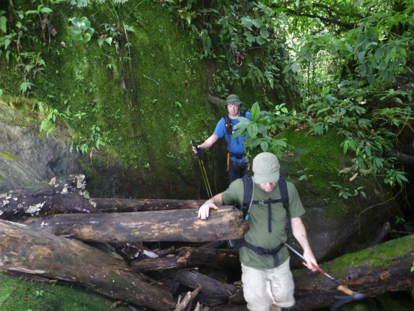 Scrambling over a log jam. You can see the rainy season water level where the moss ends on the rock. If you attempted this in the wet months the water would be chest deep, not to mention carrying tree trunks the size of telephone poles.