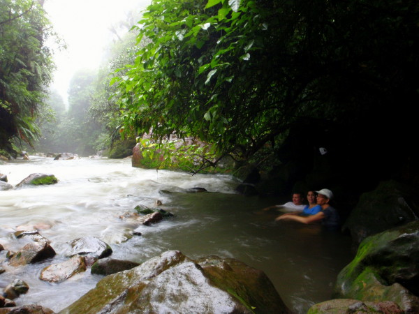 In the natural hotsprings in the rain - alongside the Rio Celeste in Volcan Tenorio National Park - with manual temperature control - move the rocks to add or reduce the mix of cool river water
