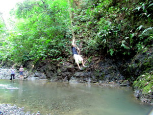 Swinging on a jungle vine into a pool in the Rio Tigre