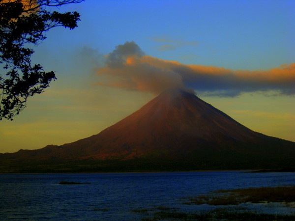 Sunset glow reflecting on Arenal volcano across the lake