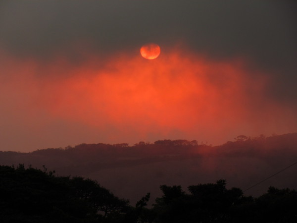 Strangely inverted upside down sunset with all the color below the sun in Monteverde. The close in clouds were hanging low cutting off the orange and red from above the sun where you normally see sunset colors.