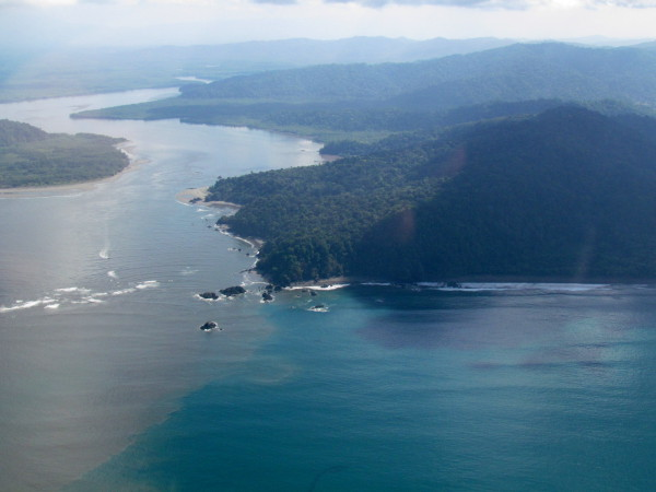 The muddy brown waters of the Sierpe river empty into the Bahia de Coronado. Isla Violin is on the left of the opening, there is a small boat in the middle of the channel on the left of the opening is playa Blanca then Punta Sierpe at the center and Playa Ganado stretching to the right. Sierpe Terraba wetlands in the background protects all five species of mangroves found in Costa Rica (black, white, red, tea and buttonwood).