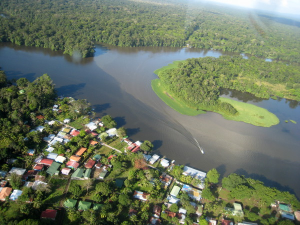 Tortuguero Village from the air. Park headquarters surround the green roofed kiosk (far left center) on the near shore where the laguna (darker water coming in from the left) intersects the oxbow of the river.