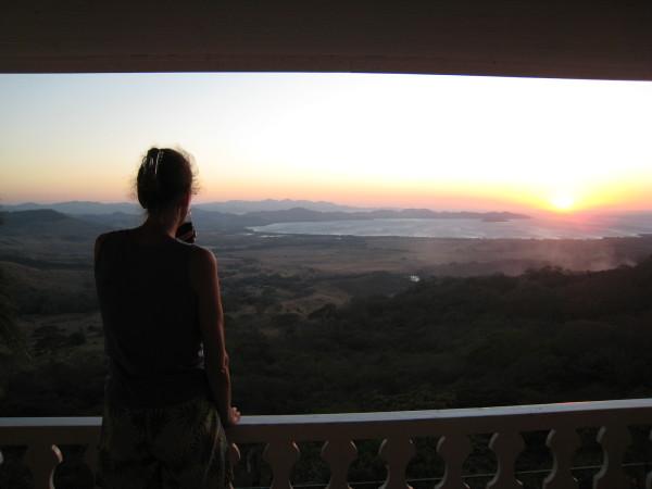 Sue silhouetted at sunset over Bahía de Salinas, Playa Pochote and Isla Bolaños National Wildlife Refuge from Amalias Inn, La Cruz